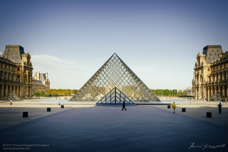 The Pyramid at the Louvre, With people walking about in the arly morning. Image contains grain. Editorial Only